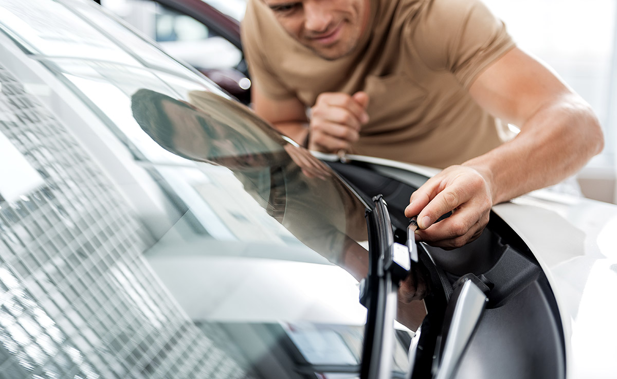 man inspecting windshield wiper